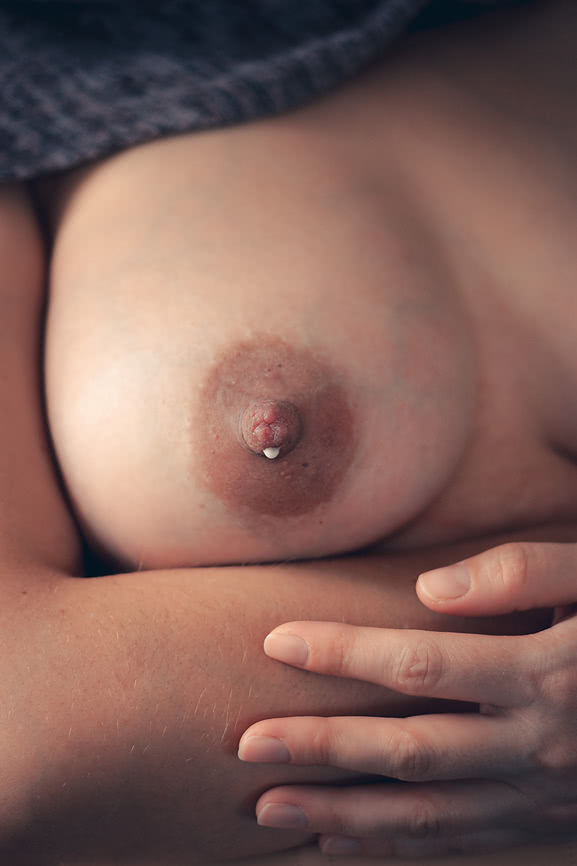 engorged breast with drop of milk coming out of nipple