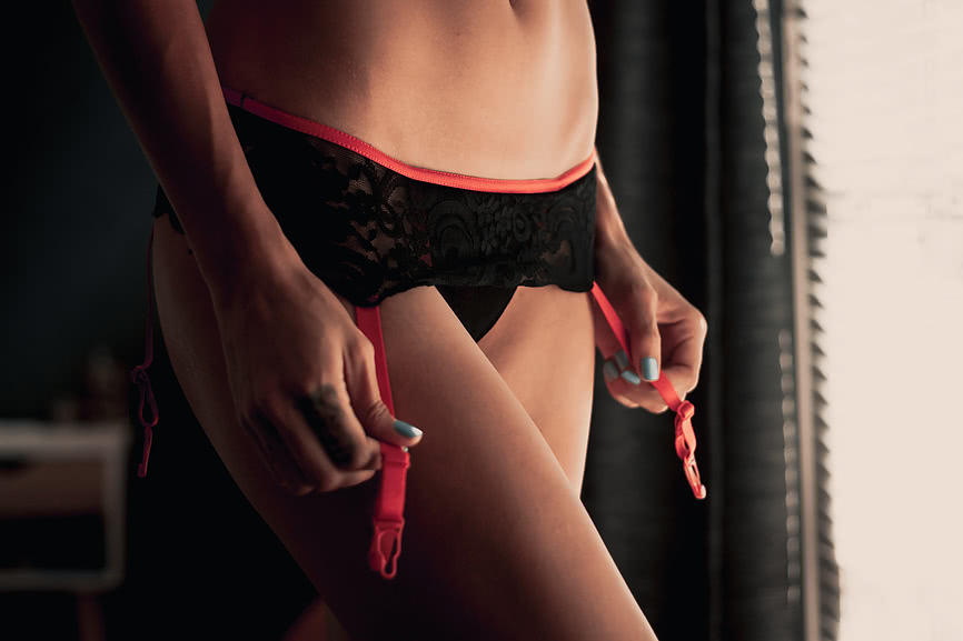 Chloe puts on her black and red garter belt