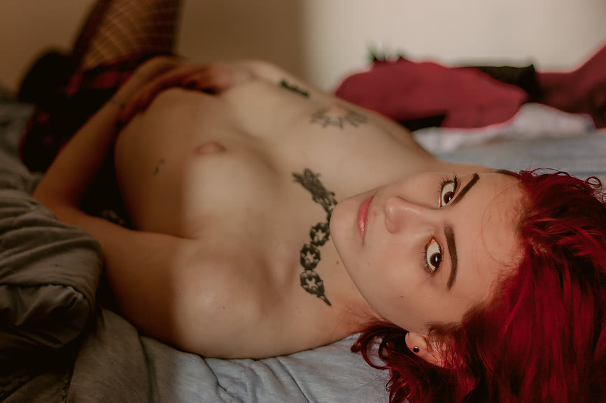 Lark Terry lying naked in her bed exposing her small breasts and bright red hair