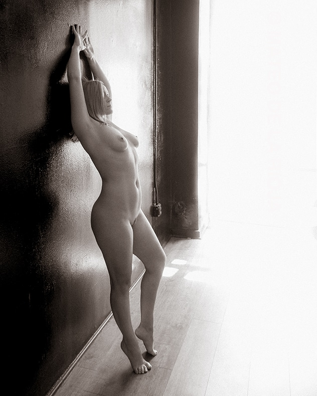 nude woman standing next to a wall as the light enters from the side