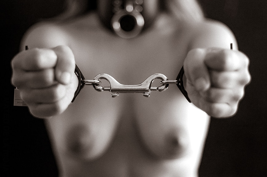 view of collared woman's nude breasts and shackled hands