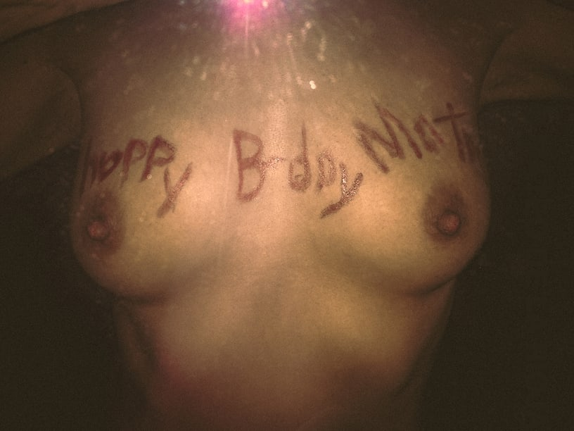 self-shot photo of nude breasts with birthday message written in them with lipstick