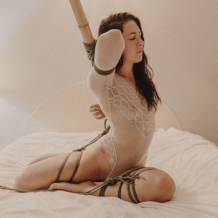 woman tied to a bamboo log in rope bondage session