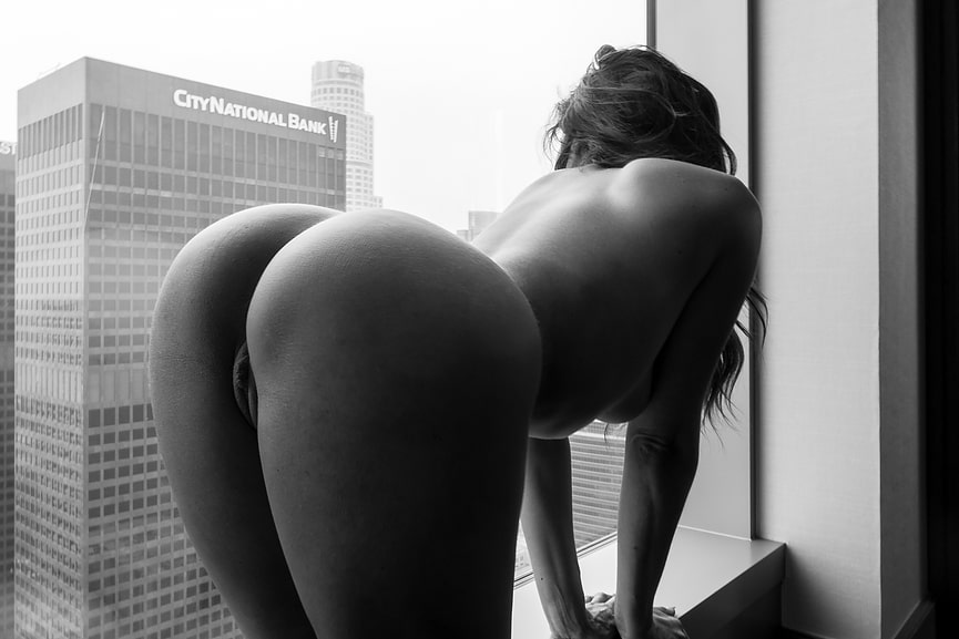 Nude Christiana Cinn crawls in all four by the window looking out to an adjacent building