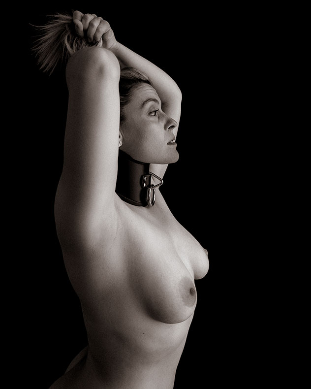 She wears a bondage collar and exposes her naked breasts
